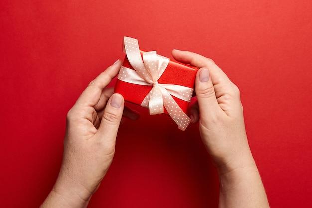 Manos sosteniendo caja de regalo sobre fondo rojo.