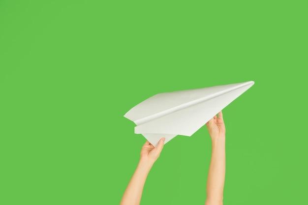 Manos sosteniendo el cartel de avión de papel o mensaje sobre fondo verde.