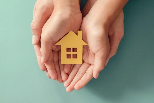 Manos sosteniendo casa de papel amarillo sobre superficie azul, hogar familiar, vivienda para personas sin hogar y seguro de protección del hogar, concepto de hipoteca, cuidado de hogar de crianza