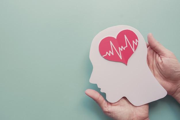 Manos sosteniendo el cerebro y el corazón de papel, día mundial del corazón