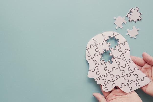 Manos sosteniendo el cerebro con recorte de papel de rompecabezas, día mundial de la salud mental
