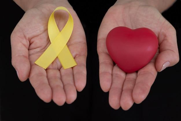 Manos sosteniendo cinta amarilla y corazón rojo campaña de prevención del suicidio de septiembre amarillo