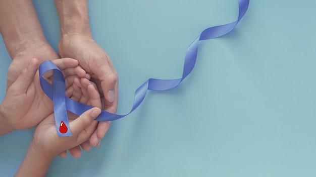 Manos sosteniendo la cinta azul con sangre roja, día mundial de la diabetes