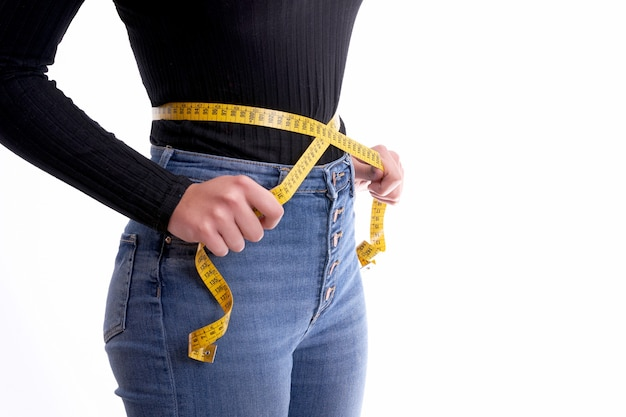 Manos sosteniendo cinta métrica alrededor del concepto de cintura, salud y dieta.