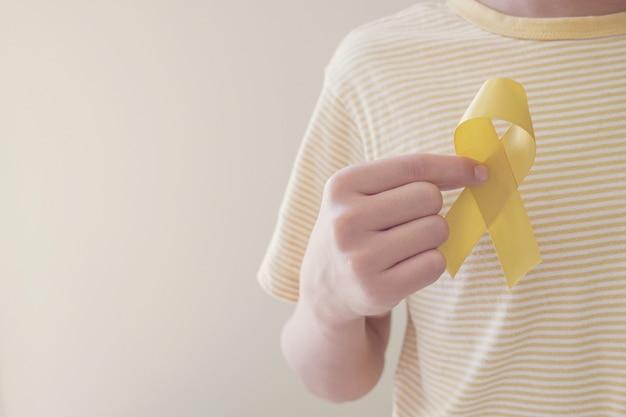 Manos sosteniendo cinta de oro amarillo, conciencia sobre el sarcoma, conciencia sobre el cáncer infantil, concepto del día mundial de prevención del suicidio