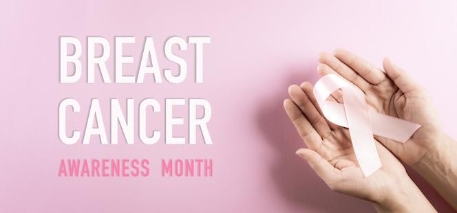 Manos sosteniendo cinta rosa conciencia del cáncer de mama color del arco simbólico