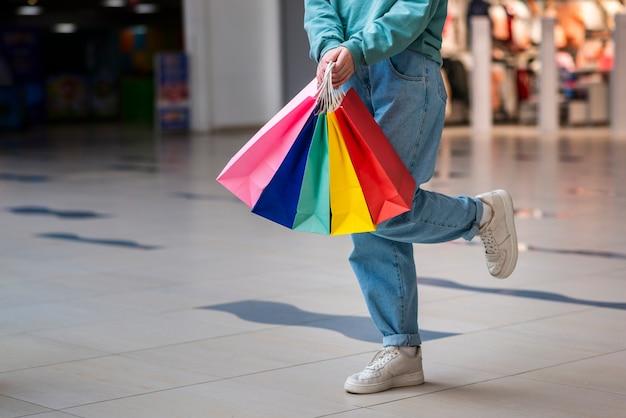 Manos sosteniendo coloridos bolsos de compras