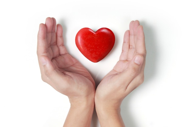 Manos sosteniendo conceptos de corazón rojo, salud del corazón y donación