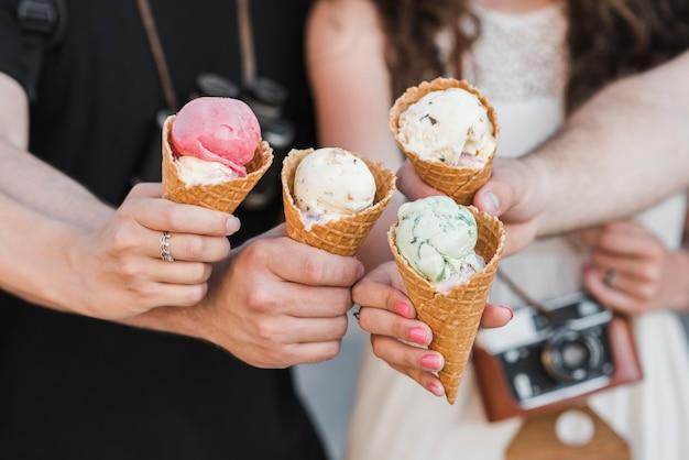 Manos sosteniendo conos de helado