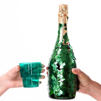 Manos sosteniendo una copa y una botella de champagne