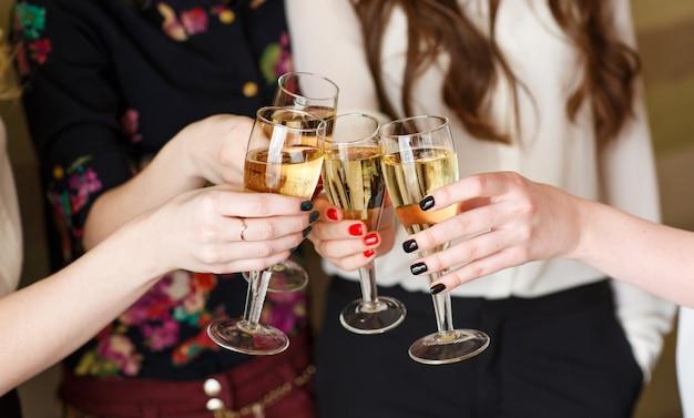 Manos sosteniendo las copas de champán haciendo un brindis
