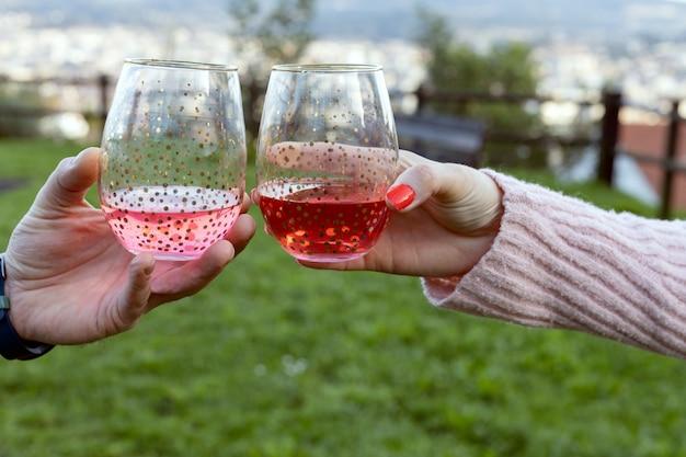 Manos sosteniendo copas de cristal