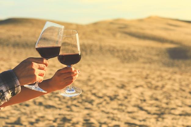 Manos sosteniendo copas de vino tinto en la duna de pyla durante la puesta de sol