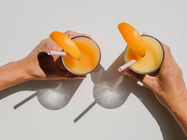 Manos sosteniendo copas con vista superior de jugo de naranja natural