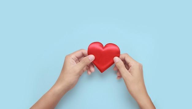 Manos sosteniendo un corazón rojo. conceptos de donación de salud del corazón