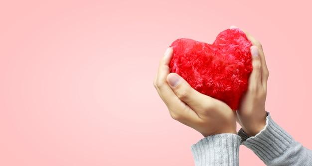 Manos sosteniendo un corazón rojo. y conceptos de donación