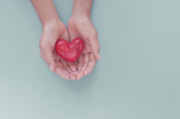 Manos sosteniendo corazón rojo, día mundial del corazón, día mundial de la salud