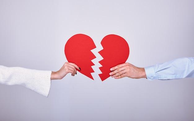 Manos sosteniendo un corazón rojo roto por la mitad.