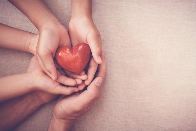 Manos sosteniendo corazón rojo, seguro de salud, concepto de donación