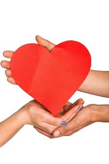 Manos sosteniendo corazón rojo