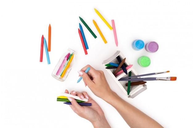 Manos sosteniendo crayones multicolores