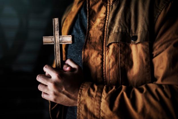 Manos sosteniendo cruz orando por dios religión