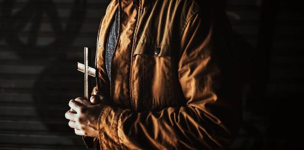 Manos sosteniendo la cruz orando por dios religión