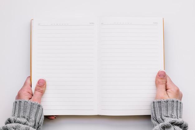 Manos sosteniendo cuaderno abierto