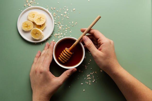 Manos sosteniendo el cuenco y el cucharón de miel