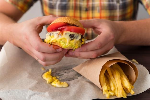Manos sosteniendo una deliciosa hamburguesa con queso