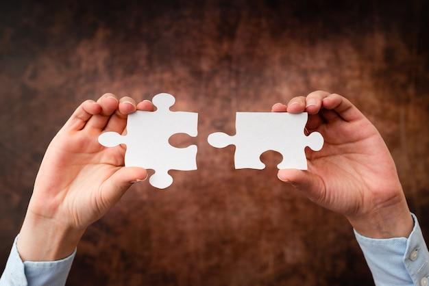 Manos sosteniendo dos piezas de rompecabezas.cooperación para encontrar y resolver ideas que faltan en el trabajo.empresario encuentra estrategia para resolver, conectar pensamientos