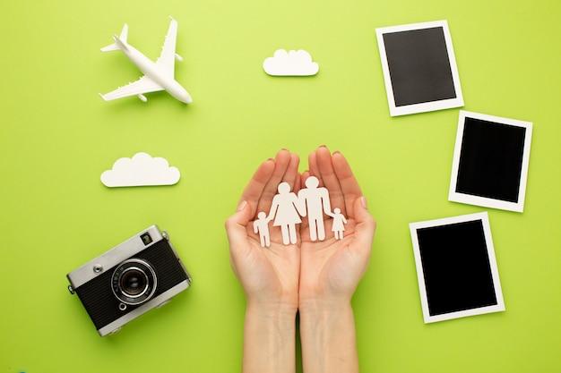 Manos sosteniendo familia de papel junto a fotos instantáneas