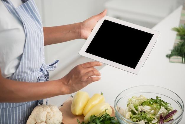 Manos sosteniendo una foto simulacro junto a verduras