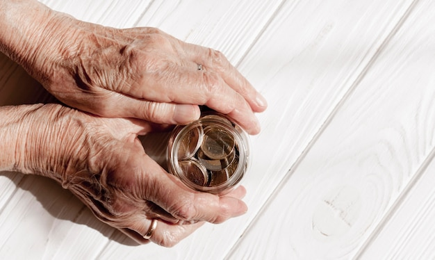 Manos sosteniendo un frasco de monedas