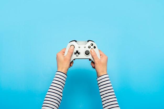 Manos sosteniendo un gamepad en un espacio azul. bandera. juegos conceptuales, videojuegos