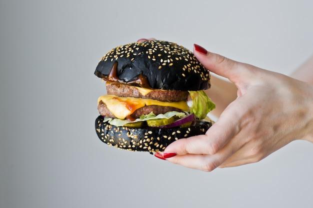 Manos sosteniendo una hamburguesa jugosa.