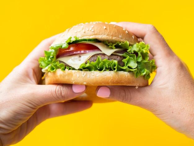 Manos sosteniendo una hamburguesa sobre fondo amarillo