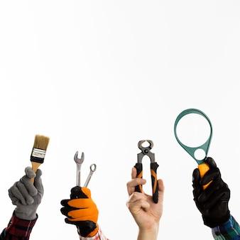 Manos sosteniendo herramientas con espacio de copia