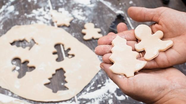 Manos sosteniendo el hombre y el árbol de navidad en forma de pastelería