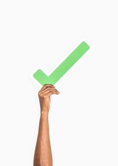 Manos sosteniendo un icono de marca de verificación