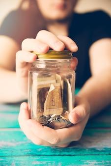 Manos sosteniendo jarra de ahorros