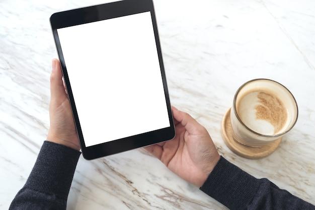 Manos sosteniendo la pc de la tableta negro con pantalla en blanco blanca y taza de café sobre fondo de tabla