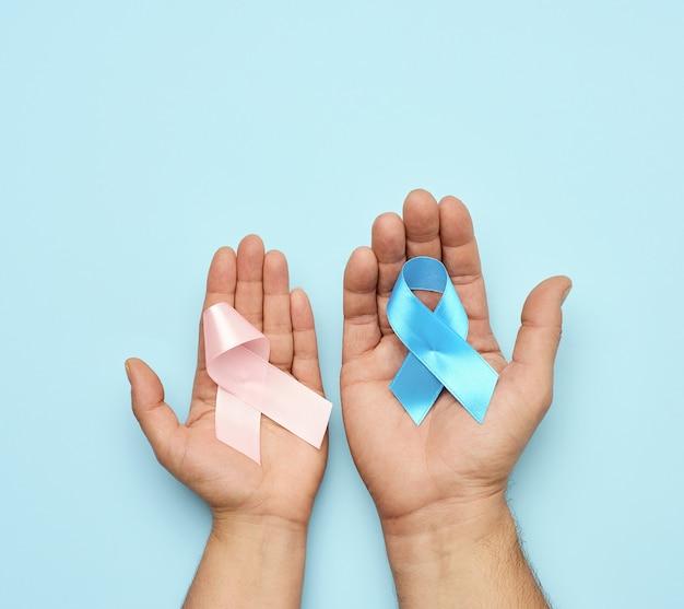 Manos sosteniendo lazo de cinta rosa y cinta azul