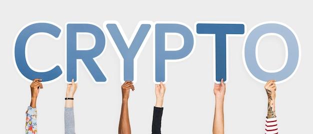 Manos sosteniendo letras azules formando la palabra crypto