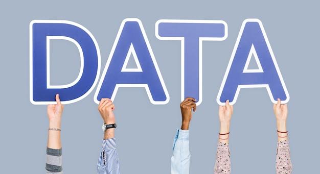 Manos sosteniendo letras azules formando la palabra datos