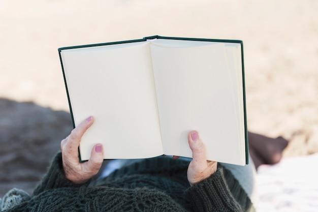 Manos sosteniendo libro en blanco
