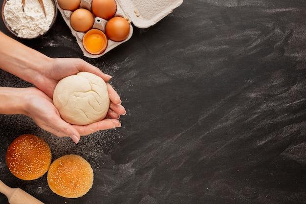 Manos sosteniendo masa con huevos y harina