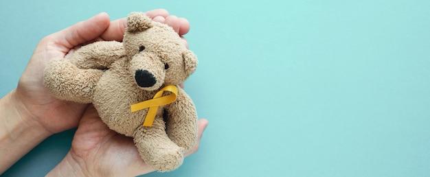 Manos sosteniendo a los niños peluche oso marrón con cinta de oro amarillo