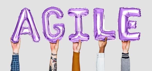 Manos sosteniendo la palabra ágil en letras globo