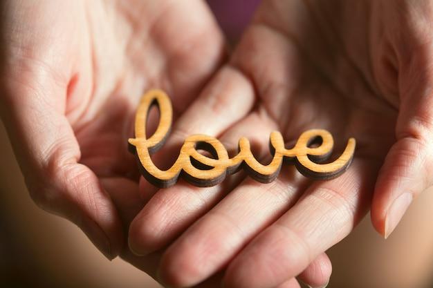 Manos sosteniendo la palabra amor